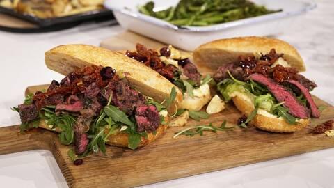 En träbricka med tre st steak sandwich, serverade med ruccola, oliver och soltorkad tomat.