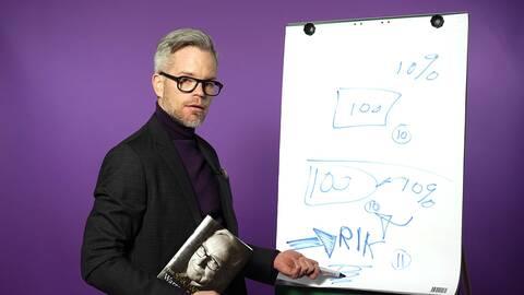 Alexander Norén framför vit tavla med bok.