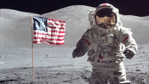 En austronaut och den amerikanska flaggan på månen.