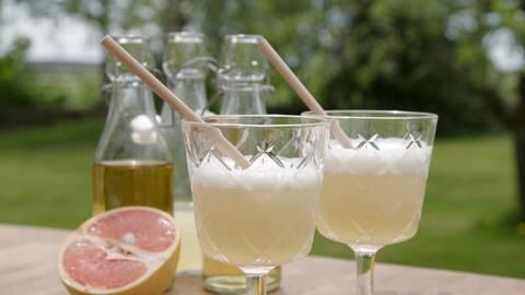 Punschdrink Diki-diki i höga glas med sugrör och en grapefrukt i bakgrunden.