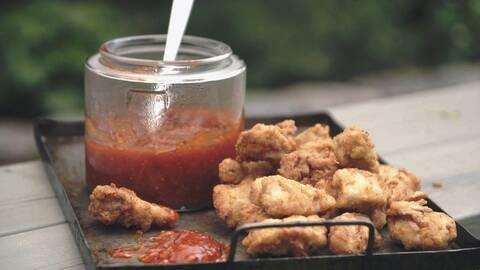 Chicken nuggets med sweet chilisås på burk och sked i burken.