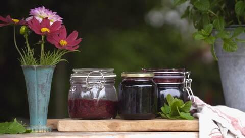 Tre burkar sylt och en kruka med tre röda blommor och en rosa blomma.