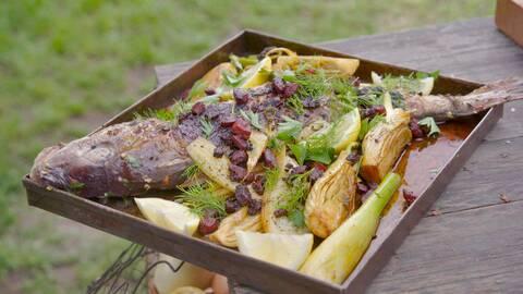 En hel grillade fisk med grönsaker, lime och fänklås i en plåt.
