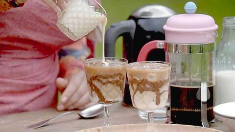 Zeina slår upp mjölk i en av de två iskaffe glasen.