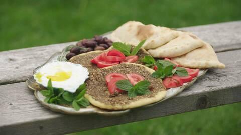 En plåt Manaish med myntor, tomater på och ägg i bredvid.