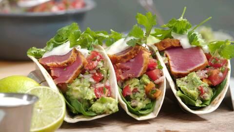 Tre tacos med topping majonnäs  och koriander och 2 lime frukter i bredvid.