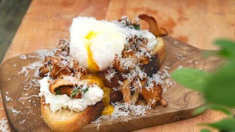 En macka med en kokt hel ägg på och topping med parmesanost på en trä skärbräda.