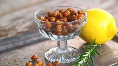 Kryddiga kikärtor i en glas skål med rosmarin och citron i bredvid.