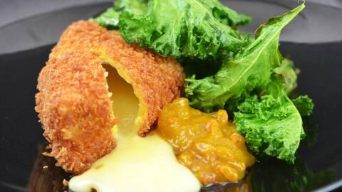Friterad camembert  med smällt ost och grönkålschips  på en svärt tallrik.