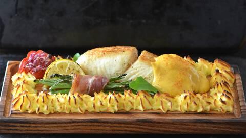 Liggande fisk, potatis mos, en bunt bönor med en baconskiva runt på en trä rektangel tallrik.