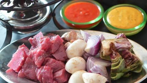 Några råa kött skivor, hela champinjoner, hackade lökar och kronärtskockor i en plått.