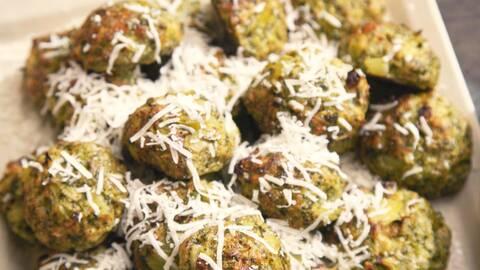 Några broccolibullar med rivna parmesan ost på en plåt.