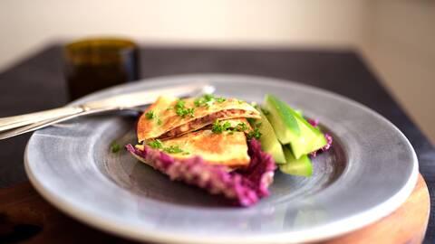 Några skivor Busenkla bönquesadillas med guacamole, finhackad koriander, sallad och en gaffel och kniv i bredvid på en tallrik.