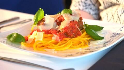 Pumpaspagetti med köttbular, tomatsås, några blad basilika och några skivor parmesan ost.