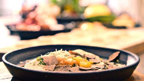 Ravioli med tryffel och parmesan på en sten djup tallrik.