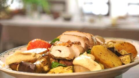 Några skivor kyckling och kokta grönsaker och potatiser på en tallrik.
