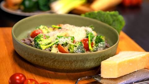 Bönpasta med broccoli , parmesan ost och grönsaker  på en skål och hel parmesan ost i bredvid.