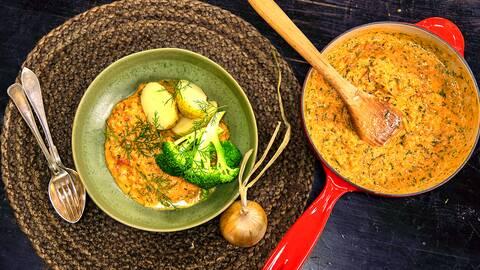 En röd stekpanna och en grön skål som är fyllda av grytan och toppning med broccoli, potatis. En sked, en gaffel  och en hel lök ligger i bredvid.