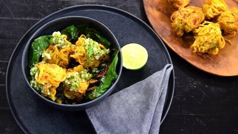 Pakoras med grön chutney och mangold i en skål och en halv lime, en servette och några pakoras på en trätallrik i bredvid.