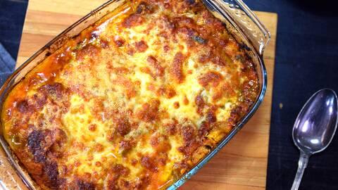 Lasagne i en ugnsform och en sked i bredvid.