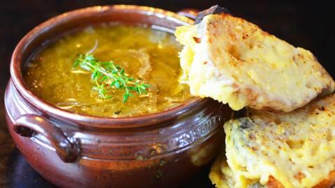Soppan i en skål med en blad timjan och två skivor bröd i bredvid.