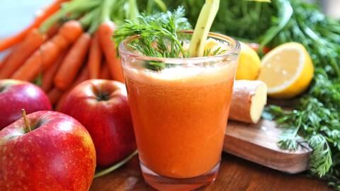 Juice med äpplen, morötter, citron och ingefära i bredvid.