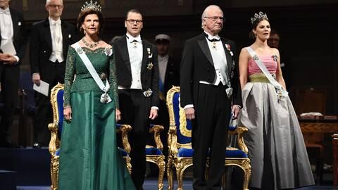 Drottning Silvia som bär på en grön klänning designad av Georg et Arend på nobelbanketten 2018. Snett bakom sig har hon svärsonen Prins Daniel och bredvid står Kung Carl XVI Gustaf. Längst till höger står kronprinsessan Victoria med en klänning som hyllades av kritikerna och som lär vara en homage till sin mor, som bar en liknande klänning på nobelgesten 1995.