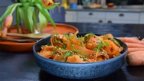 Strimlor av morot ligger i en blå skål. Råa morötter och tulpaner i fonden.