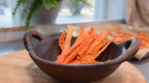 Strimlor av morötter i en brun skål med frön strösslat på.