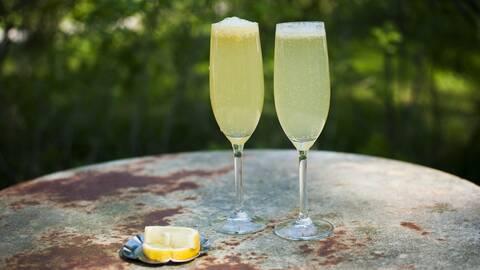 två fyllda champagneglas på plåtbord utomhus, citronskivor.
