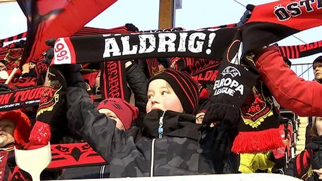 ÖFK-supportrar står och viftar med flaggor och halsdukar ovanför huvudet.