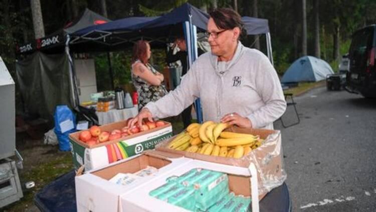 Kvinna står och gör i ordning lådor med frukt.