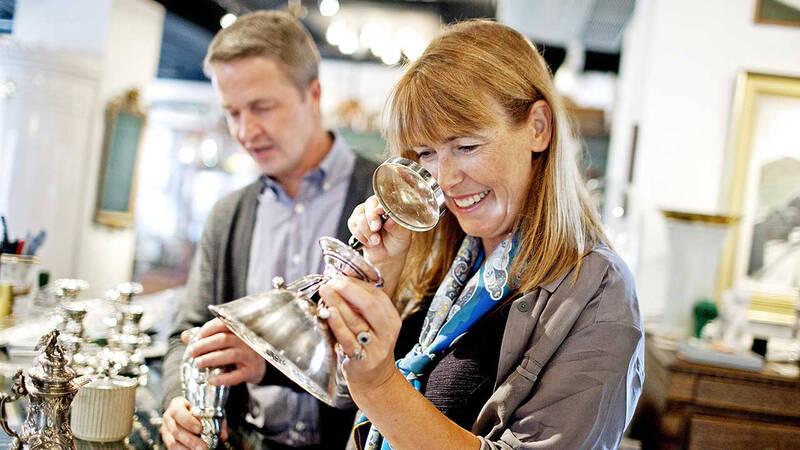 Två personer står i en antikhandel. En av dem kollar på en vas genom förstoringsglas.
