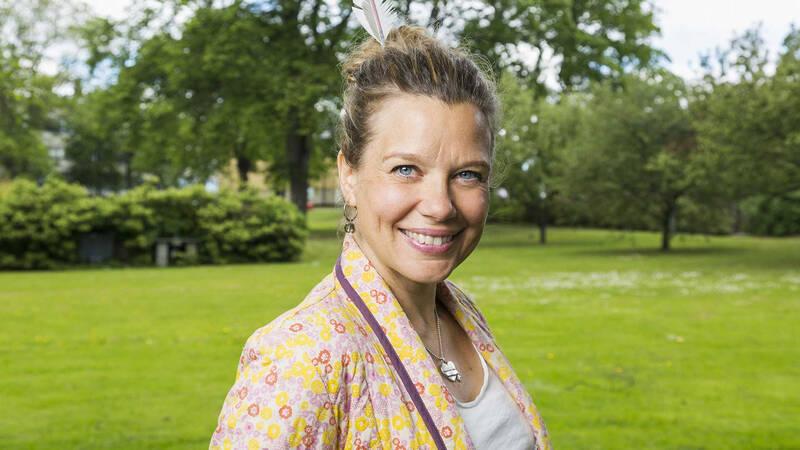 Emma Hamberg ler mot dig. I bakgrunden en grön gräsmatta.