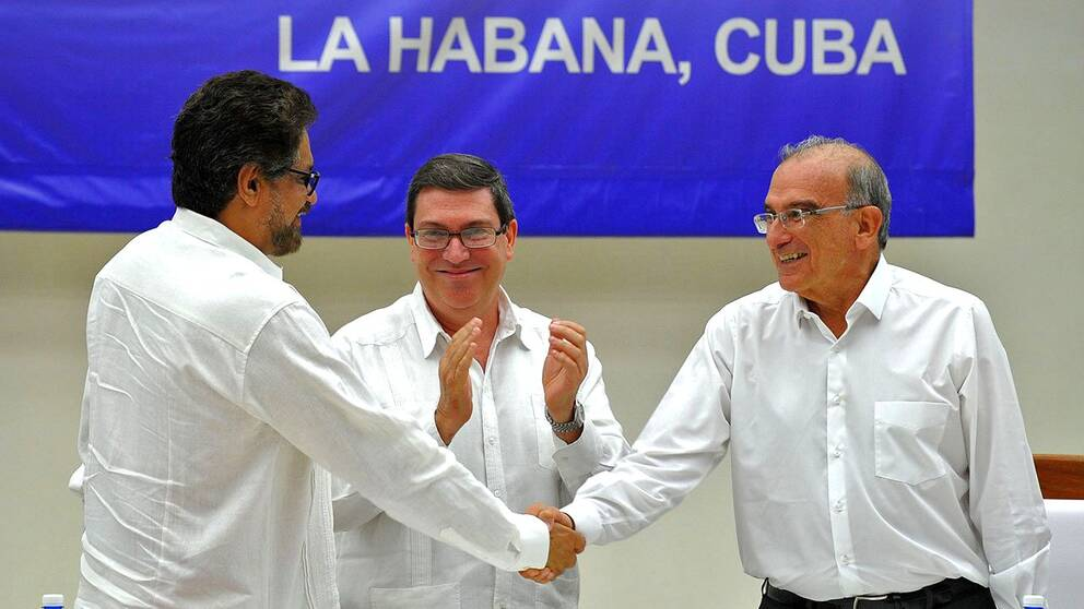 Farc-befälhavaren Ivan Marquez och den colombianska regeringens förhandlare Humberto de la Calle skakar hand efter signeringen av fredsavtalet.