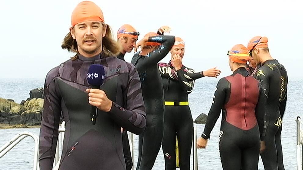 SVT:s reporter Jonathan Otter iklädd våtdräkt. Står framför flera andra personer i våtdräkt på en brygga.