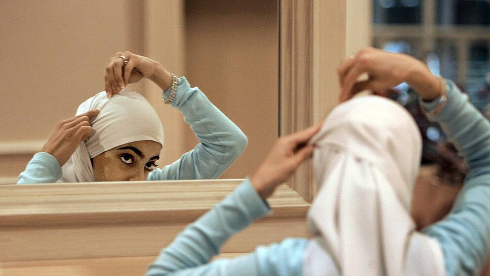 """TT-bild: """"** ADVANCE FOR FRIDAY NOV. 10 ** FILE ** Sadaf Butt, of Alabama, adjusts her hijab in a mirror at the 43rd annual Islamic Society of North America convention, Sept, 1, 2006, in Rosemont, Ill. Earlier this year on an Arabic Web site, a Muslim woman scholar posted an open letter to the Islamic world for women to take off the veil _ that head scarves and other coverings for women are not mandated by the Quran or Islamic tradition. (AP Photo/M. Spencer Green)"""""""