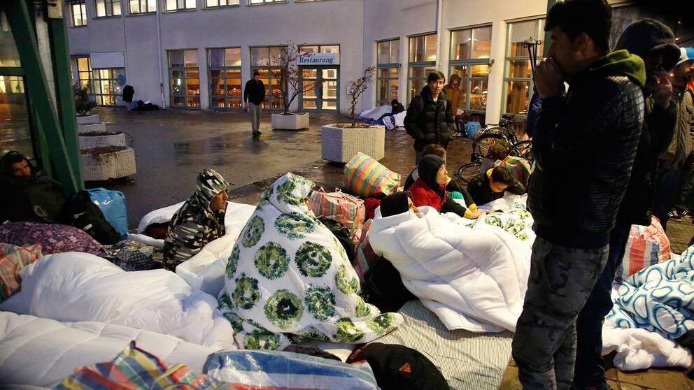 Asylsökande utanför Migrationsverkets lokaler.