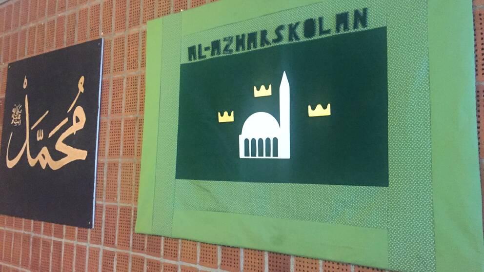 Två tygtavlor på tegelvägg. En svart med arabisk text på och en grön där det står Al-Azharskolan.