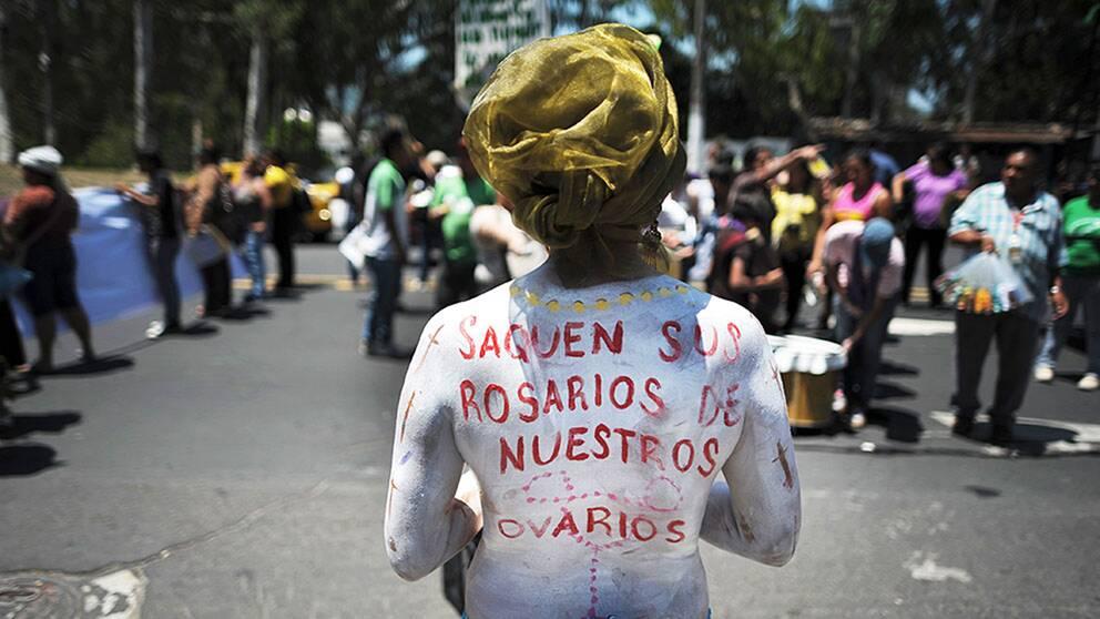 """""""Ta era radband ur våra äggstockar"""" har en kvinna skrivit på sin rygg vid en abortdemonstration i San Salvador."""