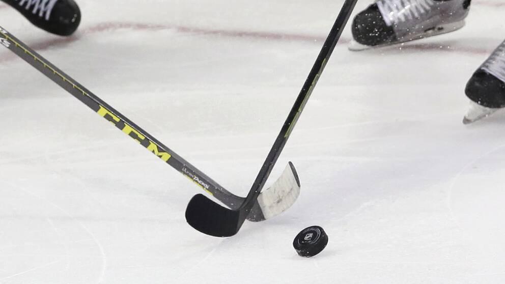 En bild på hockeyklubbor, en puck och skridskor.