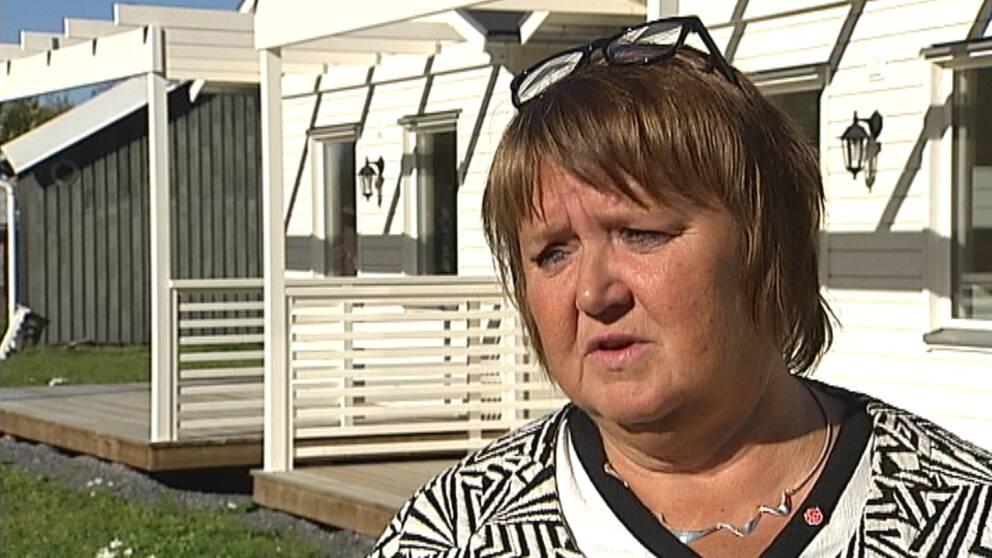 medelålders kvinna intervjuas framför hus