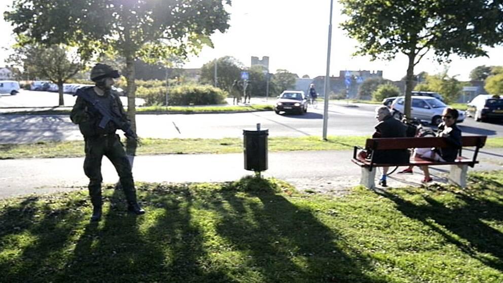 Soldat står och tittar på en parkbänk