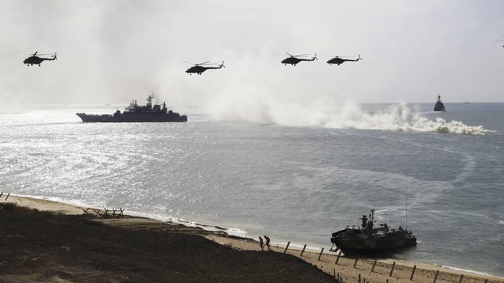 Ryska helikoptrar och fartyg övar landstigning.