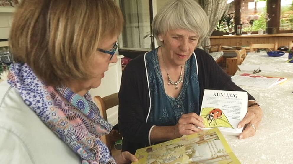 två äldre kvinnor tittar i barnböcker