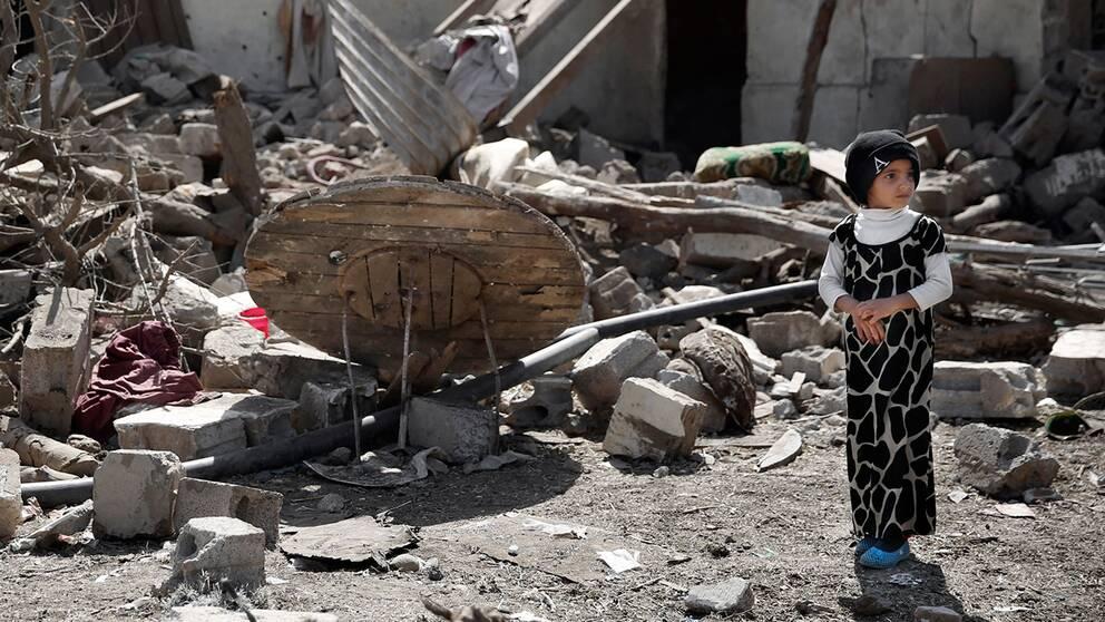 En flicka står bland resterna av ett hus efter en saudiledd flygattack i Sanaa, Jemen.