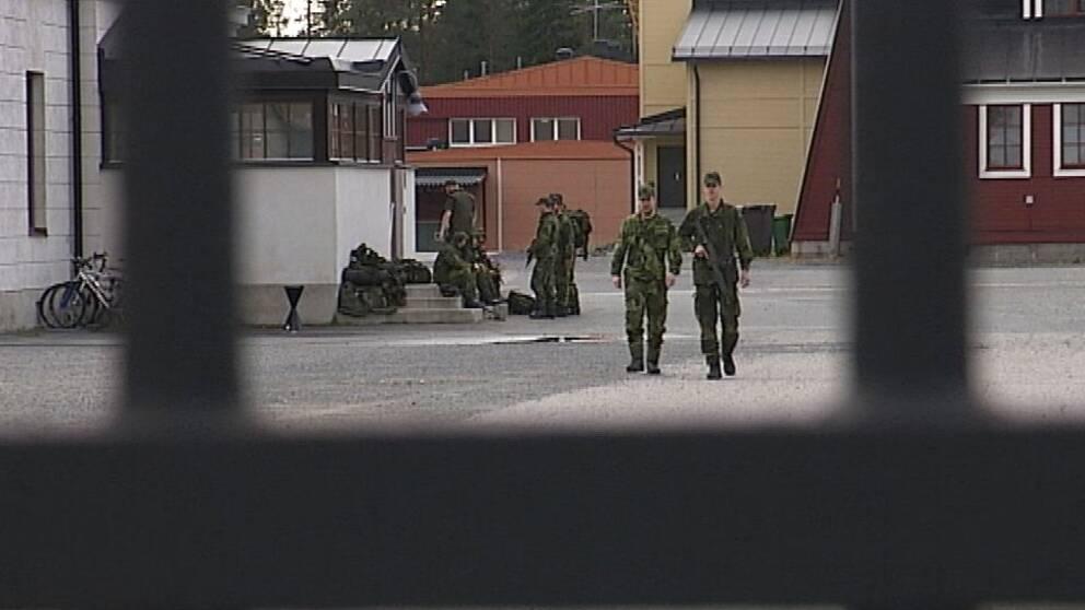Två militärer går mot grind i förgrunden