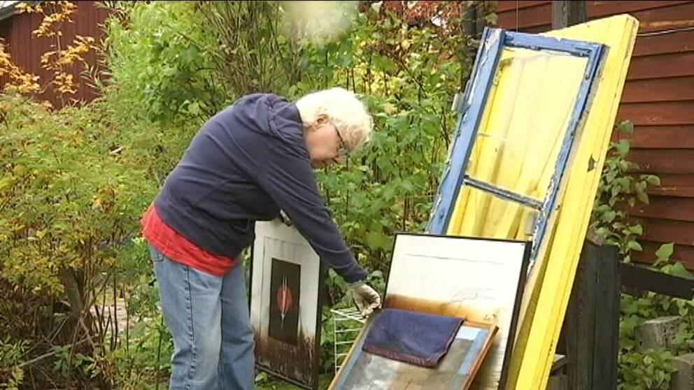 Heide Krönlein bläddrar bland tavlor som förstörts i branden