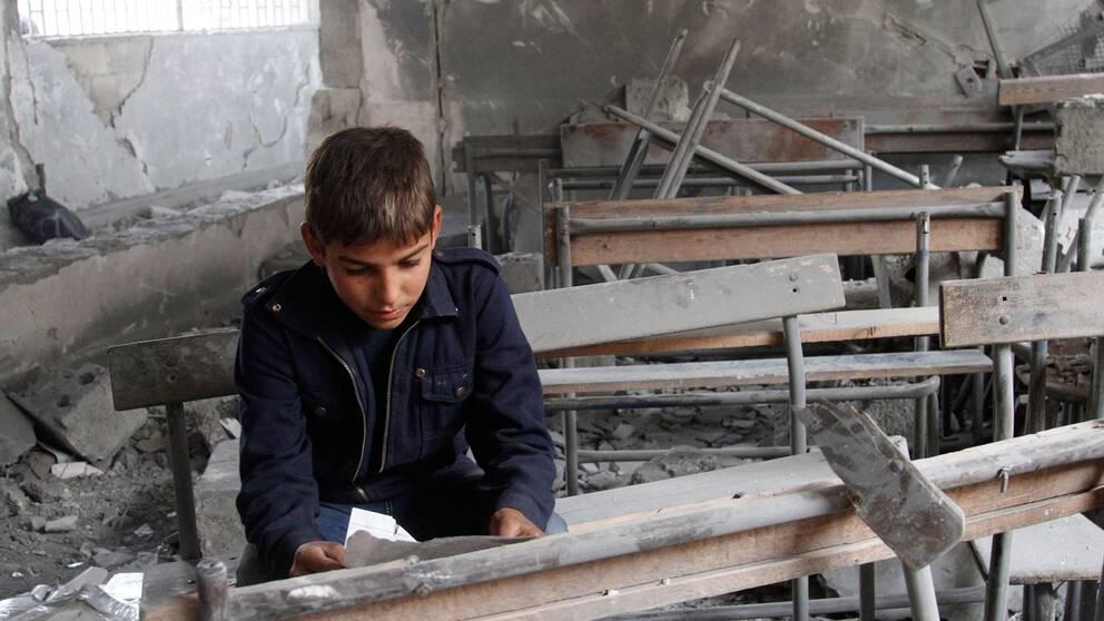 En syrisk pojke i sin sönderbombade skola i Syrien.