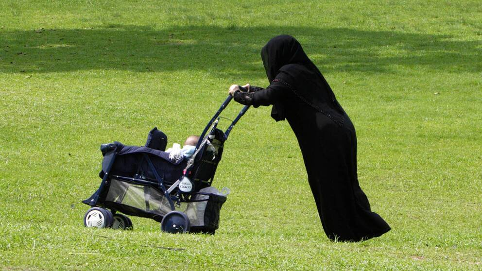 En kvinna med burka och barnvagn